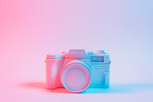 Luz azul sobre pintou uma velha câmera vintage sobre superfície rosa