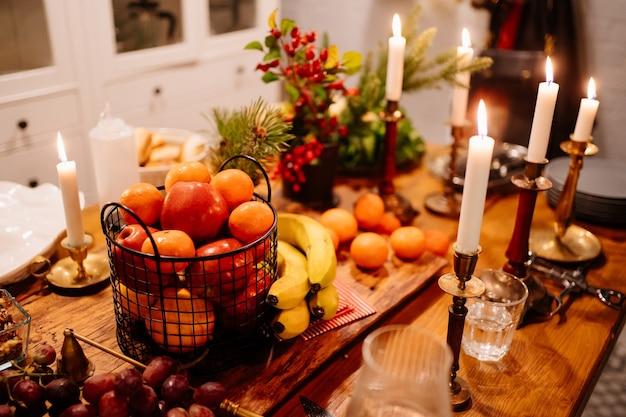 Luz baixa. tangerinas e maçãs em uma cesta de metal, velas acesas, uvas, bananas, galho de pinheiro