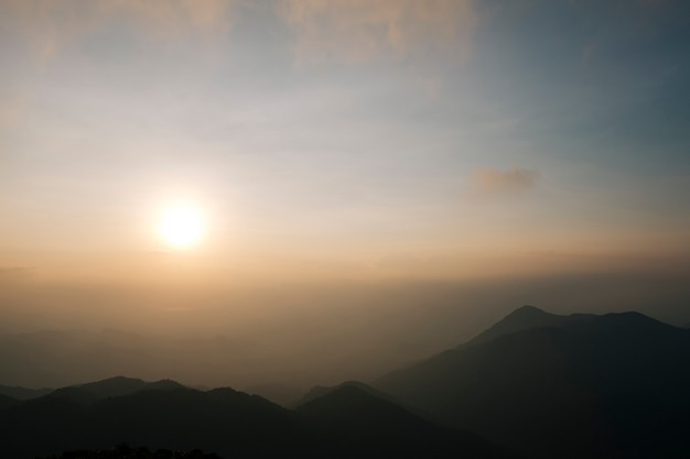 Luz da manhã nevoeiro, nascer do sol e montanhas espetaculares alinhadas alternadamente lindamente.