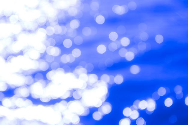 Luz da reflexão em luzes abstratas defocused do mar azul. luzes de bokeh.