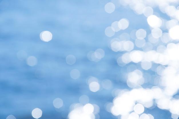 Luz da reflexão em luzes abstratas defocused do mar azul.