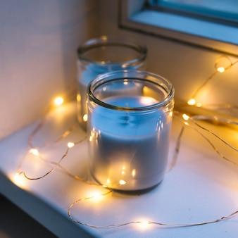 Luz de balsa de iluminação ao redor do pote de vela no peitoril da janela