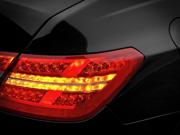 Luz de freio traseiro em um automóvel de passageiros preto. fragmento