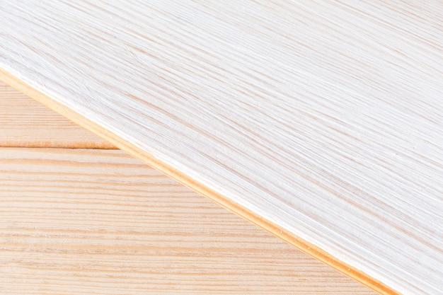 Luz de fundo de madeira para o projeto em tópicos de construção e reparação. metade do fundo é pintada de branco. disposição diagonal das placas