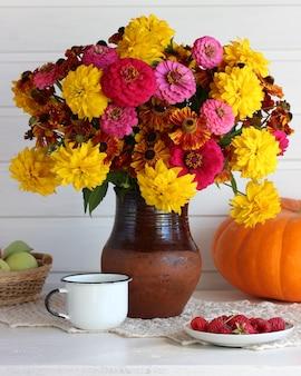 Luz de outono natureza morta com flores e frutas na mesa.