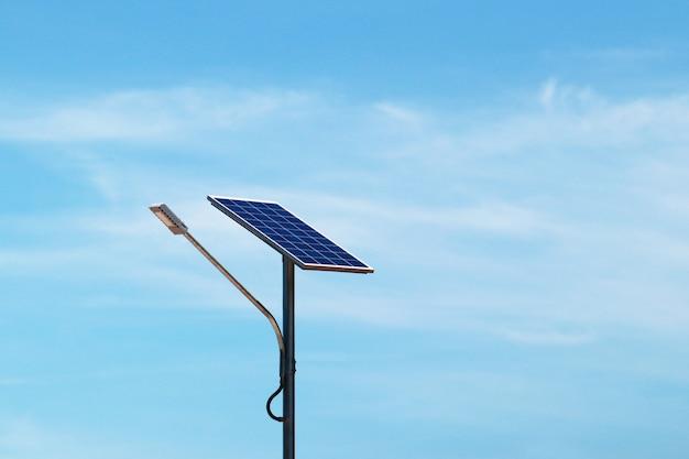 Luz de rua do diodo emissor de luz com fundo da célula solar e do céu azul.