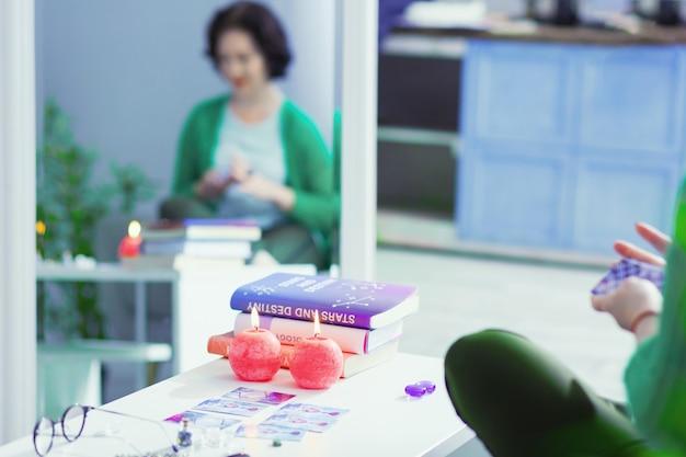Luz de velas. foco seletivo de velas acesas em cima da mesa em frente aos livros