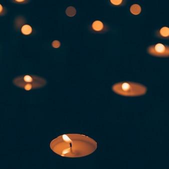 Luz de velas iluminada em pano de fundo escuro
