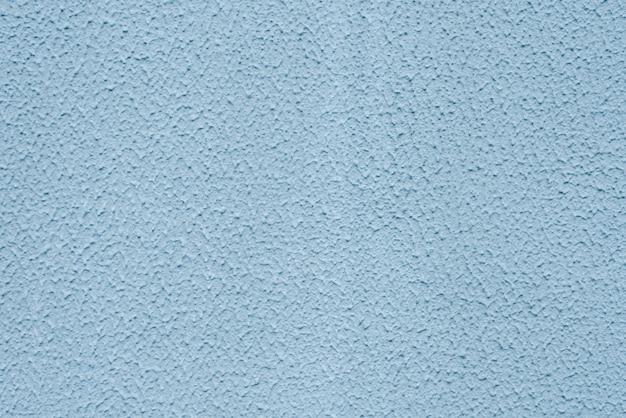 Luz decorativa abstrata de grunge - textura pintada azul do emplastro da parede.