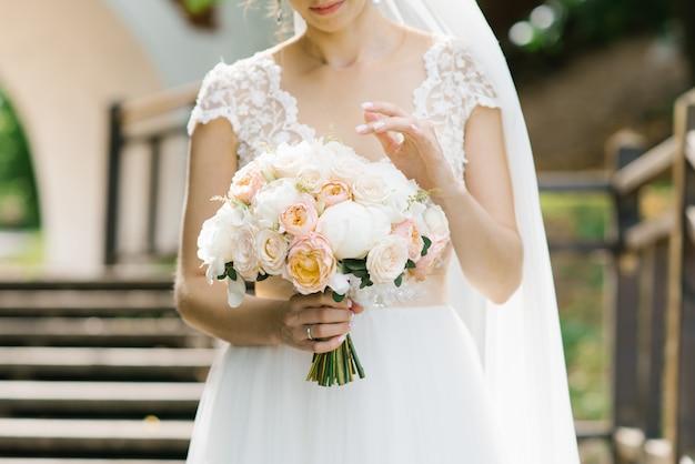Luz delicado buquê da noiva nas mãos da noiva
