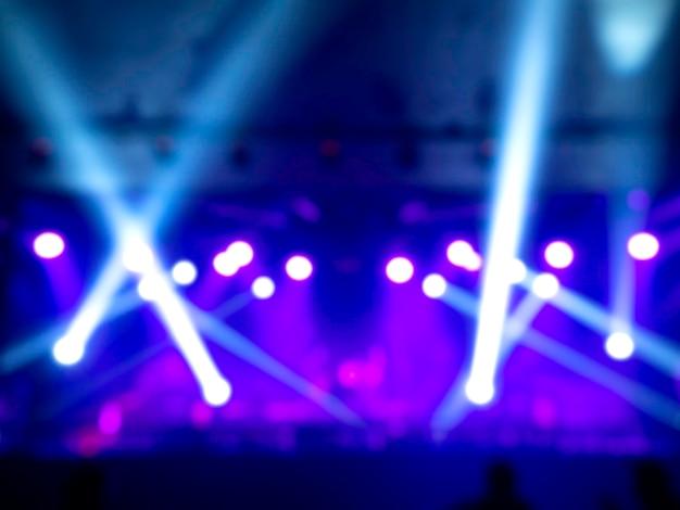 Luz desfocada de fundo de concerto com feixe colorido e raios laser no palco