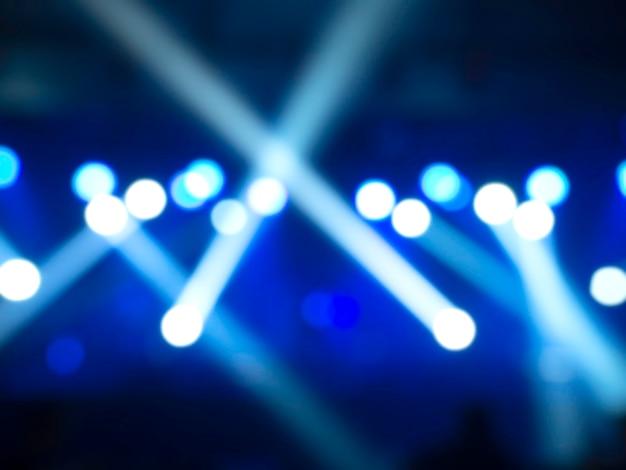 Luz desfocada de fundo de concerto com feixe de cor azul e raios laser no palco