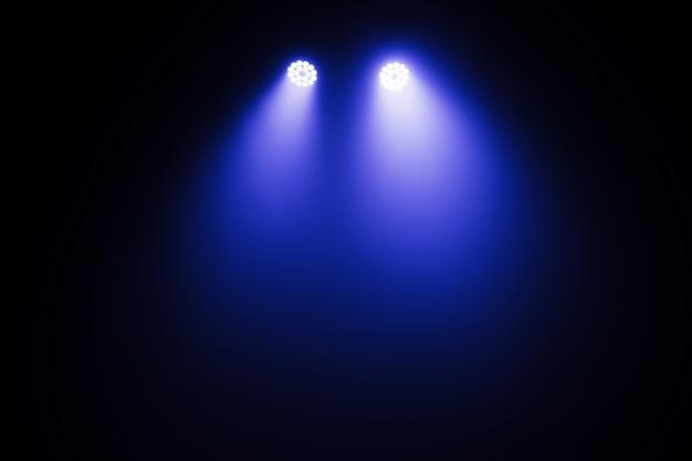 Luz do palco, luz dos holofotes através da escuridão, efeitos de luzes da cena spotlights, show de luzes no concerto.