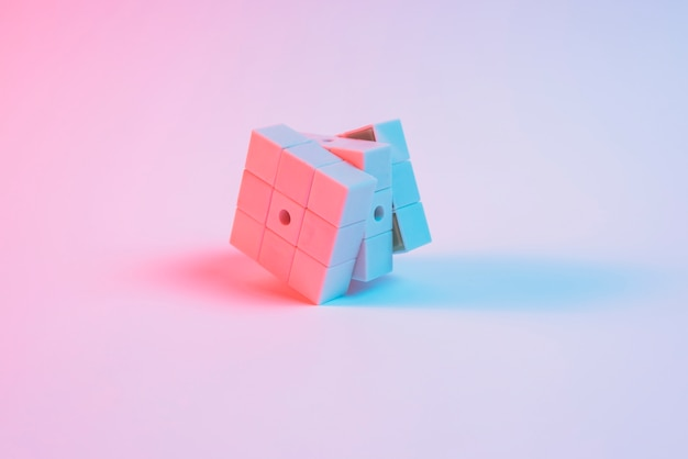 Luz do ponto azul sobre o cubo de rubik rosa no fundo liso