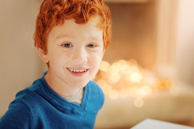 Luz do sol da família. retrato de um menino bonito de cabelo encaracolado sorrindo amplamente enquanto posava.