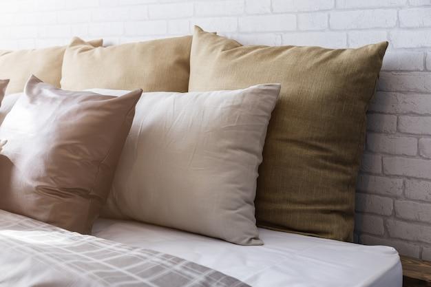 Luz do sol da manhã em travesseiros brancos limpos e lençóis no quarto