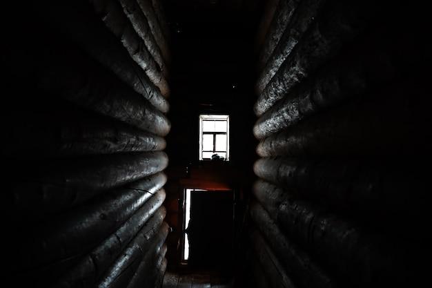 Luz do sol entrando pela janela de madeira em um antigo quarto escuro