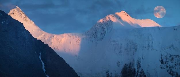 Luz do sol nas montanhas, lua cheia sobre os picos. panorama, montanha belukha, altai.