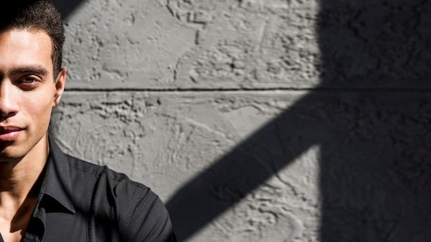 Luz do sol sobre o jovem contra a parede de concreto com sombra