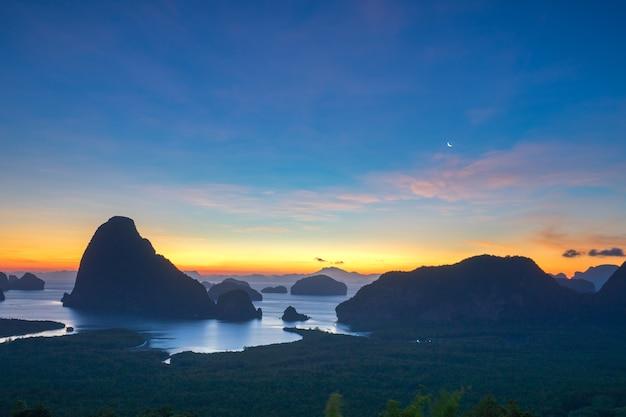 Luz dourada brilha no mar durante o nascer do sol. samet nangshe viewpoint, phang nga, tailândia