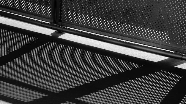 Luz e sombra de malha de arame no pavimento - monocromático
