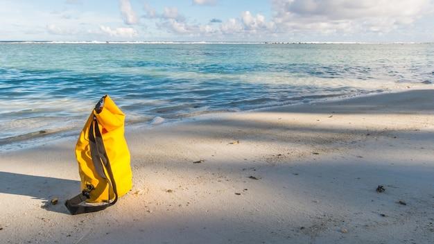 Luz e sombra na areia da praia com saco amarelo impermeável