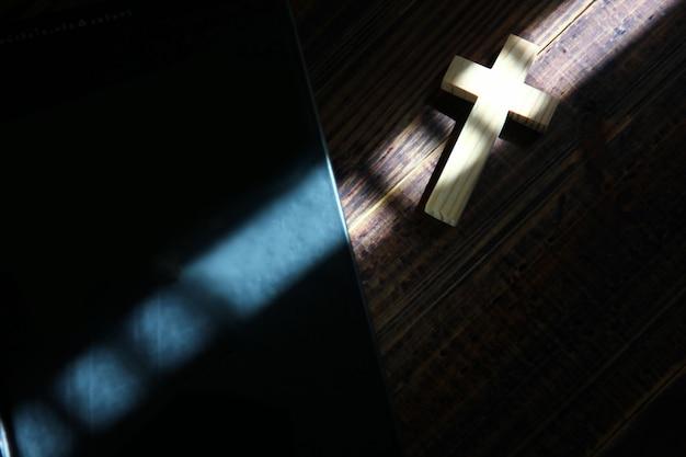 Luz e sombra na cruz de madeira e a bíblia no piso de madeira retrô