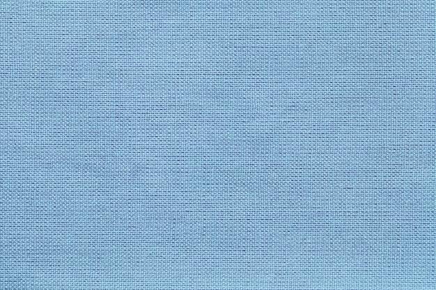 Luz - fundo azul de um material de matéria têxtil com teste padrão de vime, close up.