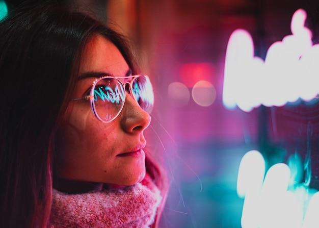 Luz neon refletida nos óculos femininos