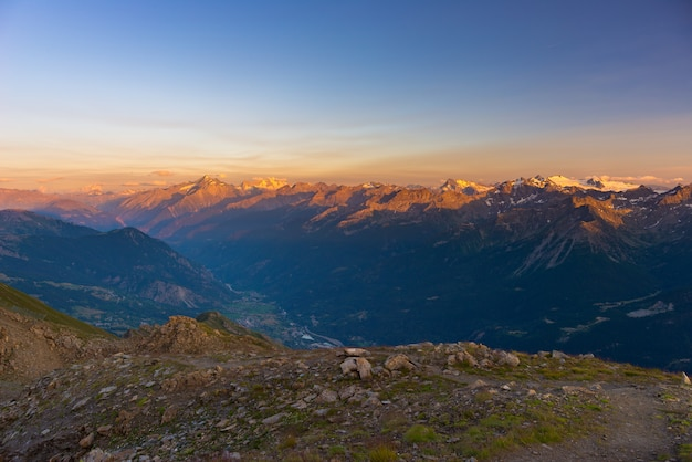Luz quente ao nascer do sol em picos de montanha, cordilheiras e vales