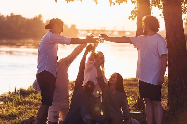 Luz quente grupo de amigos a tilintar em copos de cerveja durante um piquenique na praia ao sol