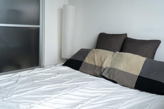 Luz solar cama de cama com almofadas brancas limpas e cama no quarto