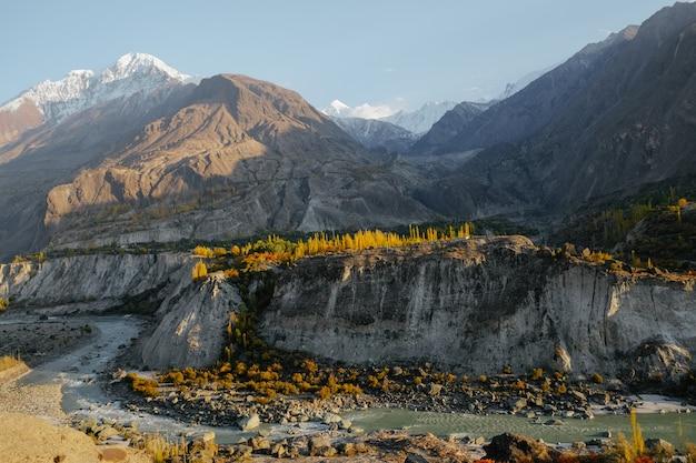 Luz solar que brilha em árvores e no rio coloridos contra picos de montanha tampados neve na escala de karakoram.