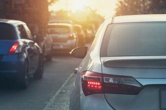 Luz traseira de carro na estrada com pôr do sol