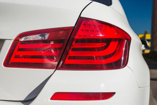Luz traseira moderna no automóvel branco novo na rua