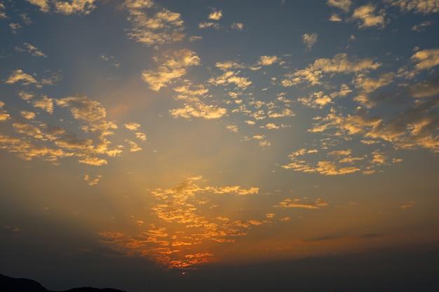 Luz vermelha e laranja na nuvem antes do pôr do sol no mar na tailândia