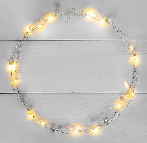 Luzes amarelas de natal festão borda circular com espaço de cópia em cinza. cores do ano 2021.