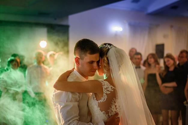 Luzes azuis e amarelas brilham em torno do casamento casal dançando na primeira vez