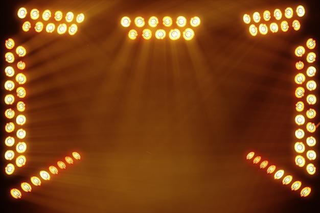 Luzes brilhantes do palco piscando no lugar da cor laranja para o seu espaço de cópia de texto