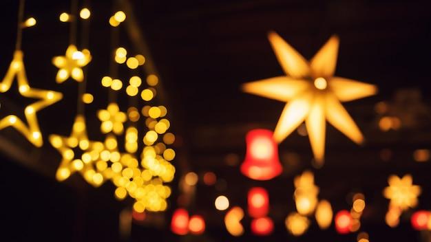 Luzes coloridas à noite borraram luzes de festa estrela bokeh abstrato da lâmpada colorida no bar e restaurante.