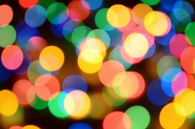 Luzes coloridas festivas turvas sobre preto