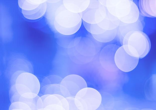 Luzes coloridas no fundo vermelho. feriado bokeh. resumo de natal, blur luz azul e branca