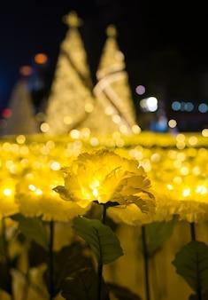 Luzes conduzidas da flor amarela da tela do cravo-de-defunto com bokeh das árvores de natal do ouro
