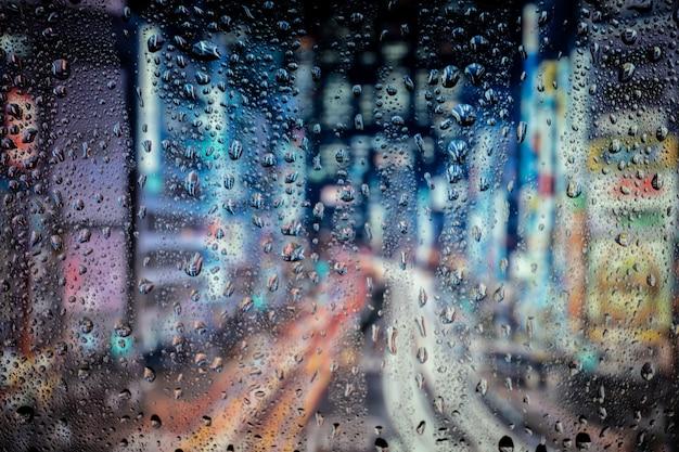 Luzes da cidade à noite pela janela com água da chuva e gotas.
