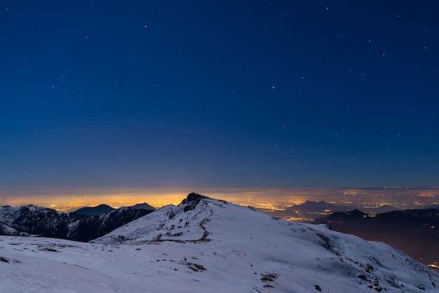 Luzes da cidade de turin, opinião da noite dos cumes cobertos de neve pelo luar.
