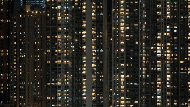Luzes da janela no bloco de apartamentos de arranha-céus à noite