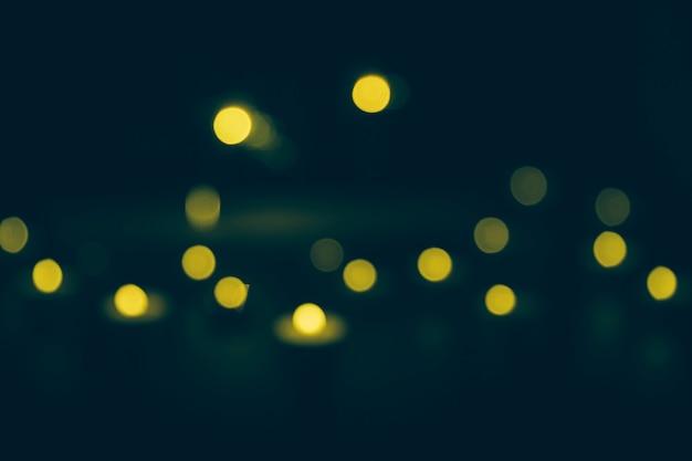 Luzes de bokeh amarelo desfocado em fundo escuro