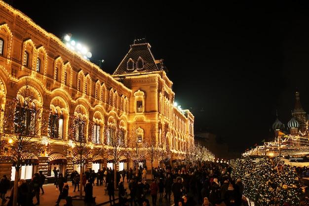 Luzes de celebração e decorações na praça vermelha para o natal festivo e ano novo. brilhando luzes amarelas na fachada goma em moscou, rússia. paisagem urbana de noite de moscou