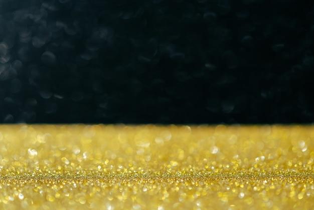 Luzes de glitter dourados com bokeh abstrato em fundo verde profundo.