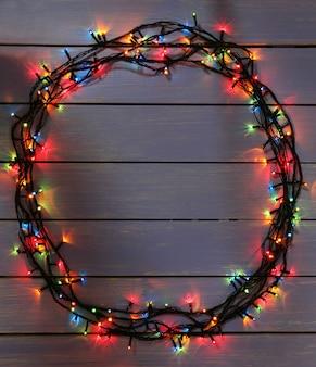 Luzes de natal coloridas em fundo de pranchas de madeira